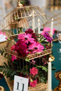dekoracja ślubna kwiaty w złotej klatce